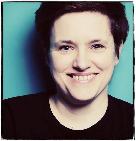 Ihre Fotografin in Dortmund. Petra Coddington - Portraitfotografie. Hier Frau vor türkiser Wand. fotograf Fotostudio Dortmund