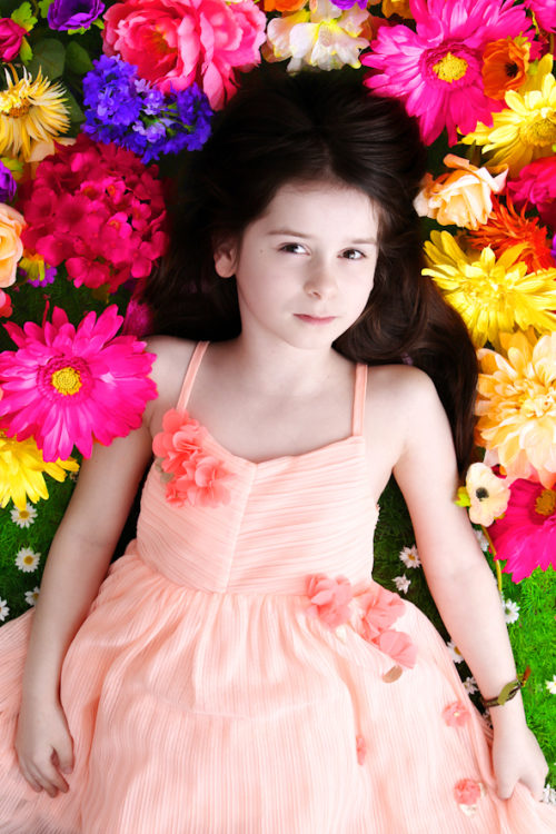 Fotostudio kreative Kinderfotos junges Mädchen liegt auf Blumen farbenfrohes Kinderbild Kinderfotos Dortmund Fotografin