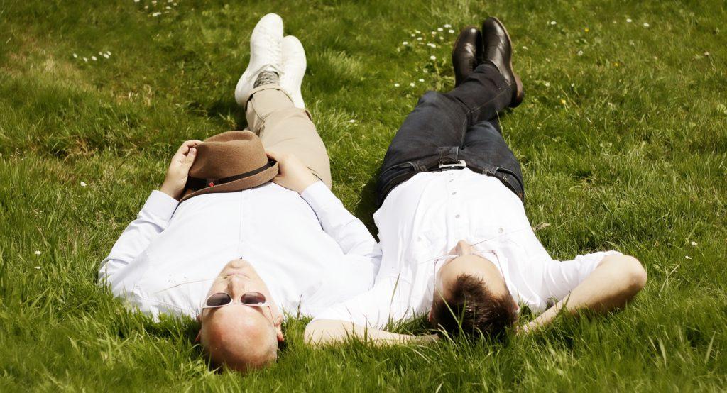 Fotostudio Dortmund Paarportrait 2 Männer liegen auf dem Rücken im Gras Fotoshooting Outdoor Fotograf