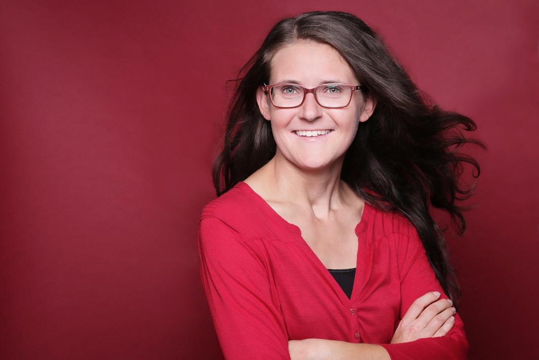 junge Frau in roter Bluse vor rotem Hintergrund Profilbild professionelle Bewerbungsfotos Ihre Fotografin in Dortmund.