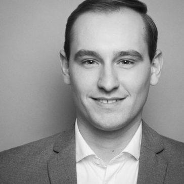 professionelle Bewerbungsfotos schwarz weiß sw. Ihre Spezialistin in Dortmund. Junger Mann auf grauem Hintergrund. Schwarz-weiß quadratisches Bewerbungsfoto Kopf angeschnitten