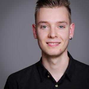Bewerbungsfotos Dortmund junger Mann grauer Hintergrund