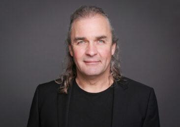 Bewerbungsfotos Headshot Mann schwarzes Jacket dunkler Hintergrund