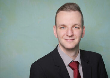 Bewerbungsfotos junger Mann mit Krawatte vintage Hintergrund blau grün