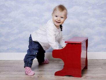 Kinderfotos kleines Mädchen mit rotem Klavier