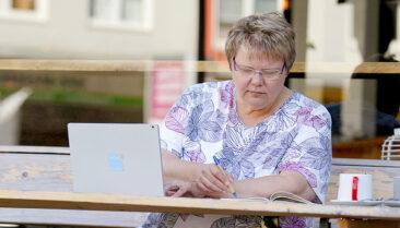 Personal Branding Fotografie Frau vor Cafe mit Laptop