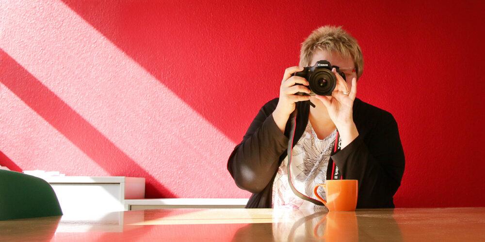 Personal Branding Fotografie Frau mit Kamera vor roter Wand