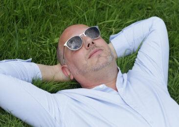 Portraitfotos Mann im Gras liegend